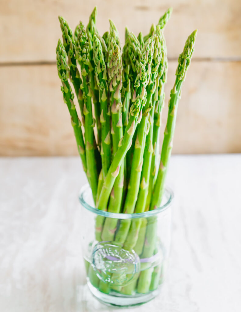 raw asparagus in a glass with water