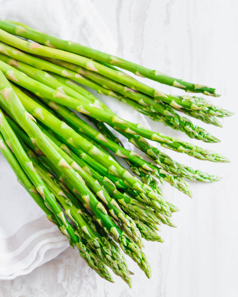 raw asparagus laid out on a kitchen cloth.