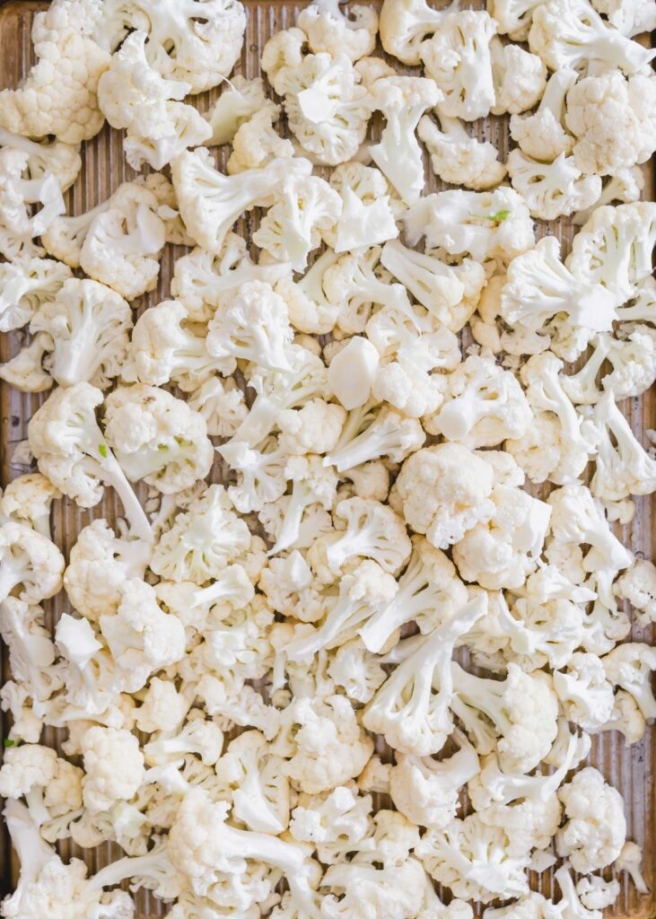 Cauliflower florets on a baking sheet.