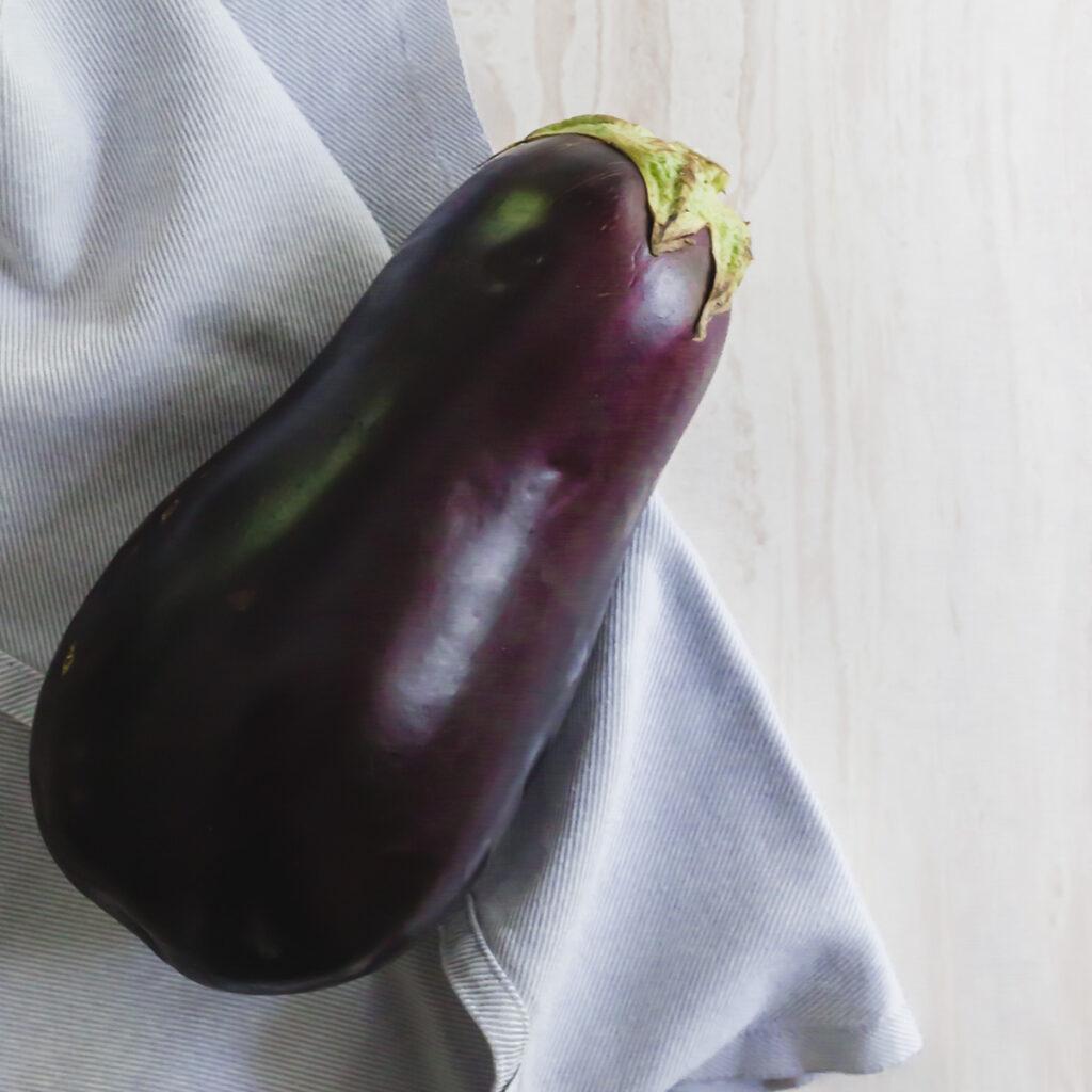 Whole eggplant on a kitchen towel.