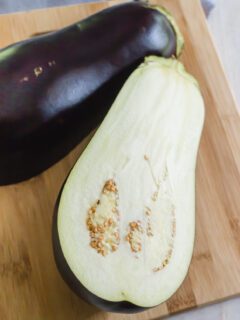 can dogs eat eggplant? - eggplant sliced in half on a cutting board
