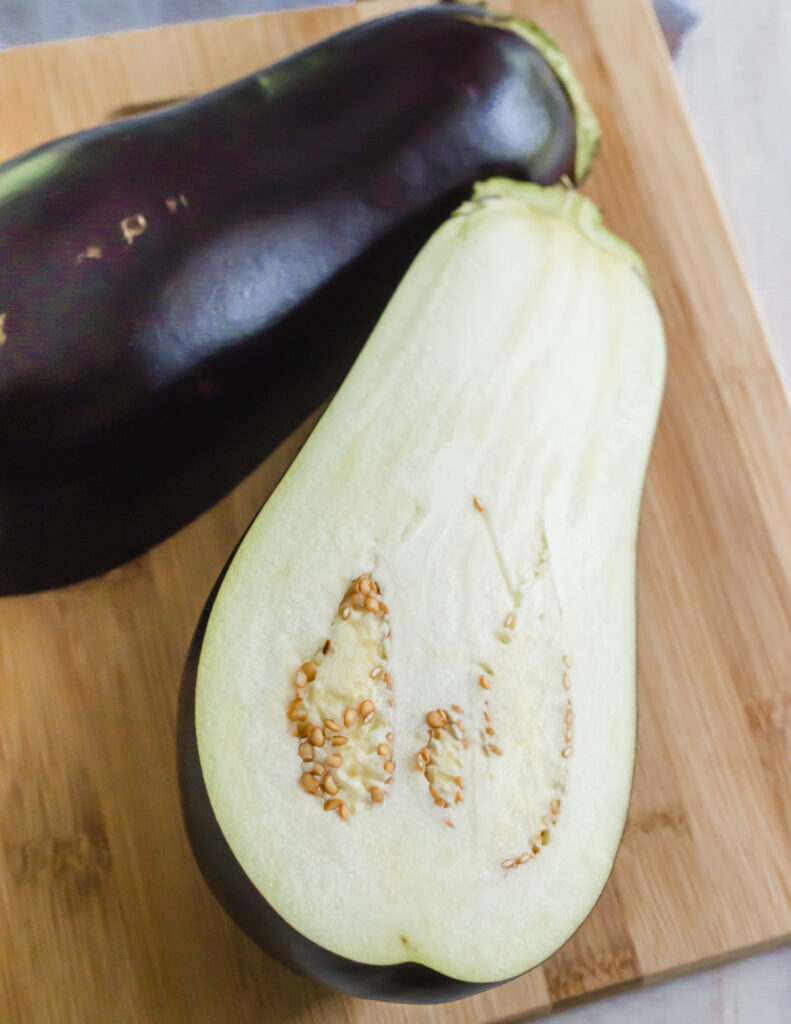 Can dogs eat eggplant? - eggplant sliced in half on a cutting board.