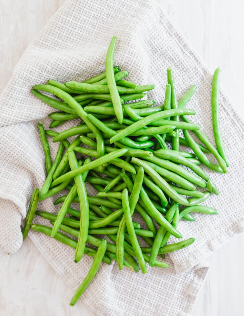 One pound of trimmed and washed green beans on a kitchen towel.