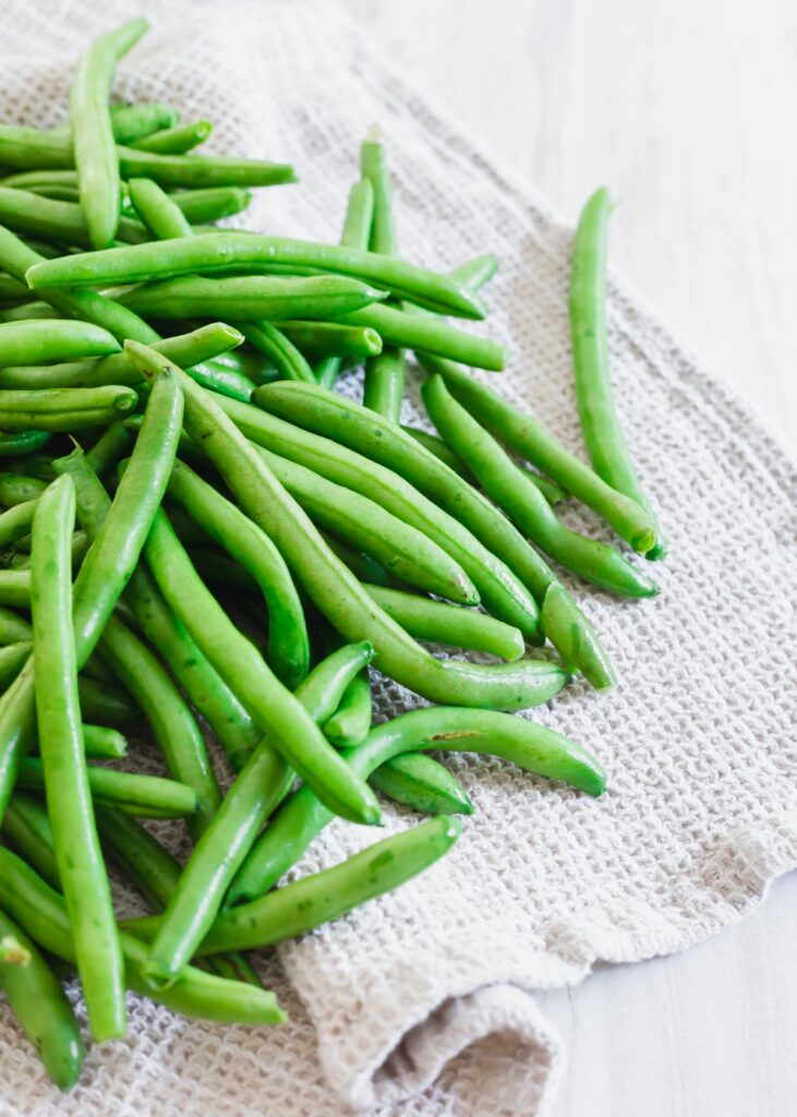 Raw washed organic green beans on a kitchen towel.