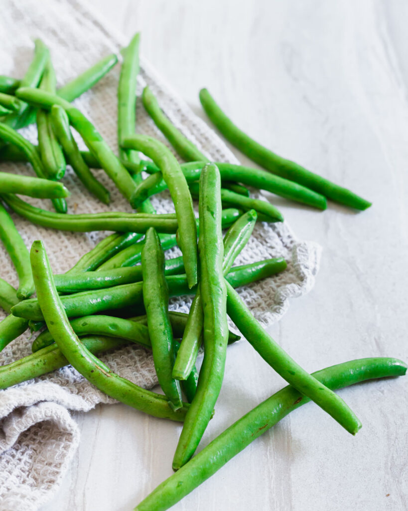 Can dogs eat green beans? - Raw washed green beans on table surface with kitchen towel.