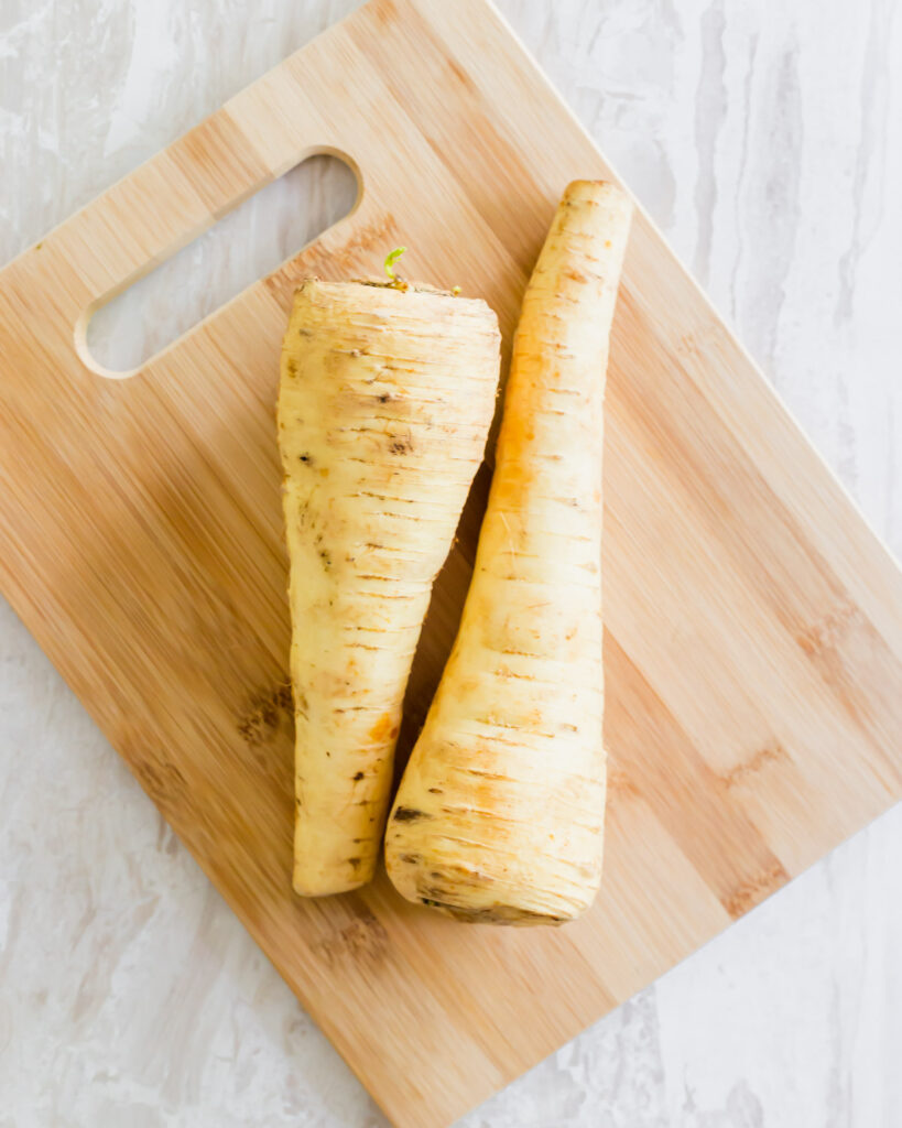 Two parsnips on a cutting board.