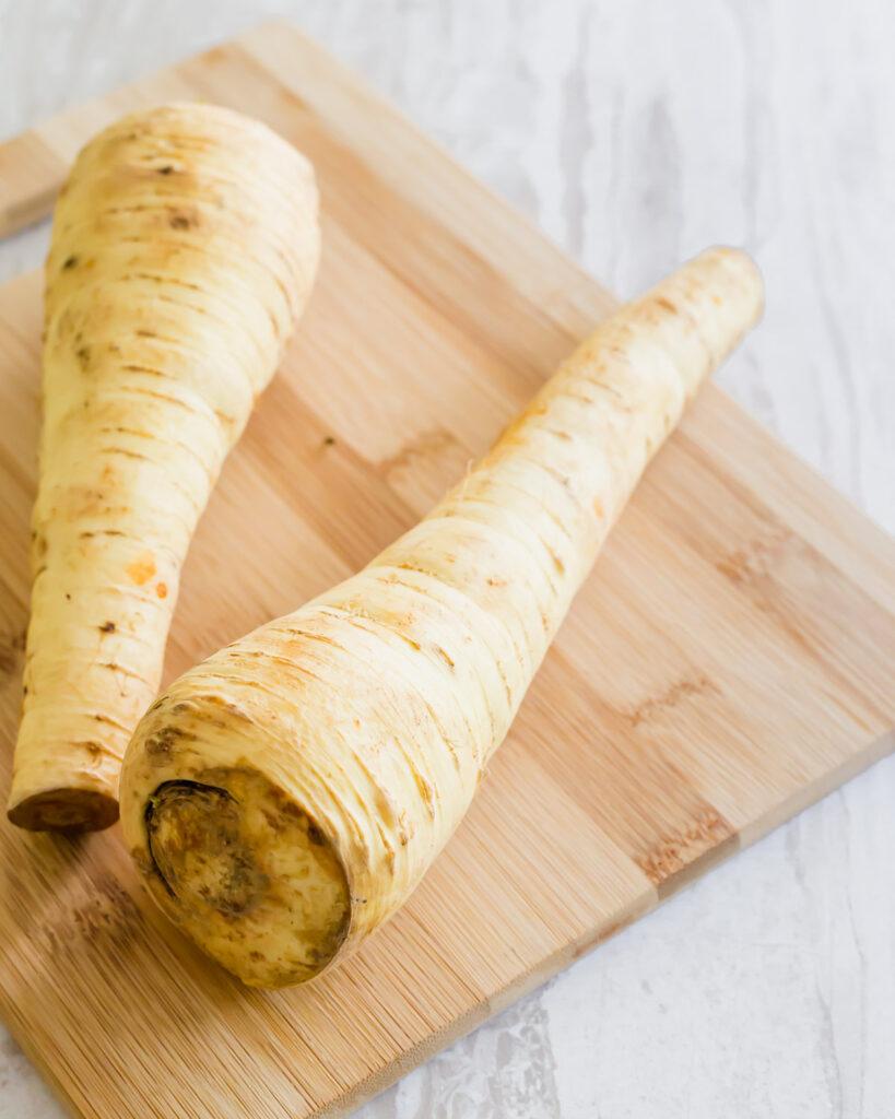 Medium sized parsnips on a cutting board.
