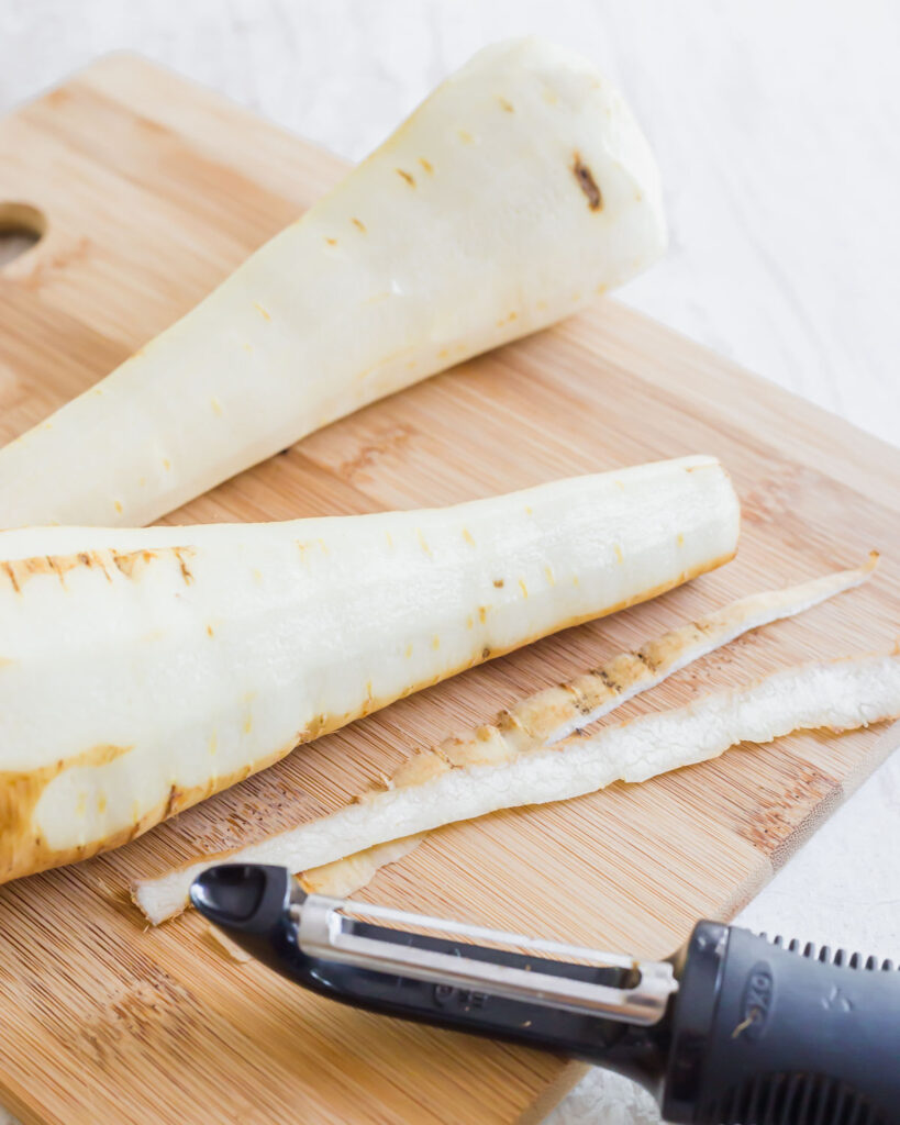Peeled parsnips on a cutting board.