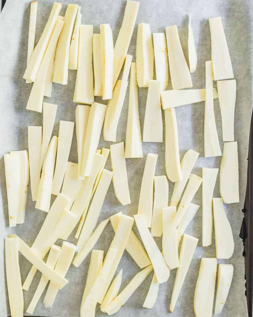 """Peeled parsnips cut into """"fries"""" on a parchment lined baking sheet."""