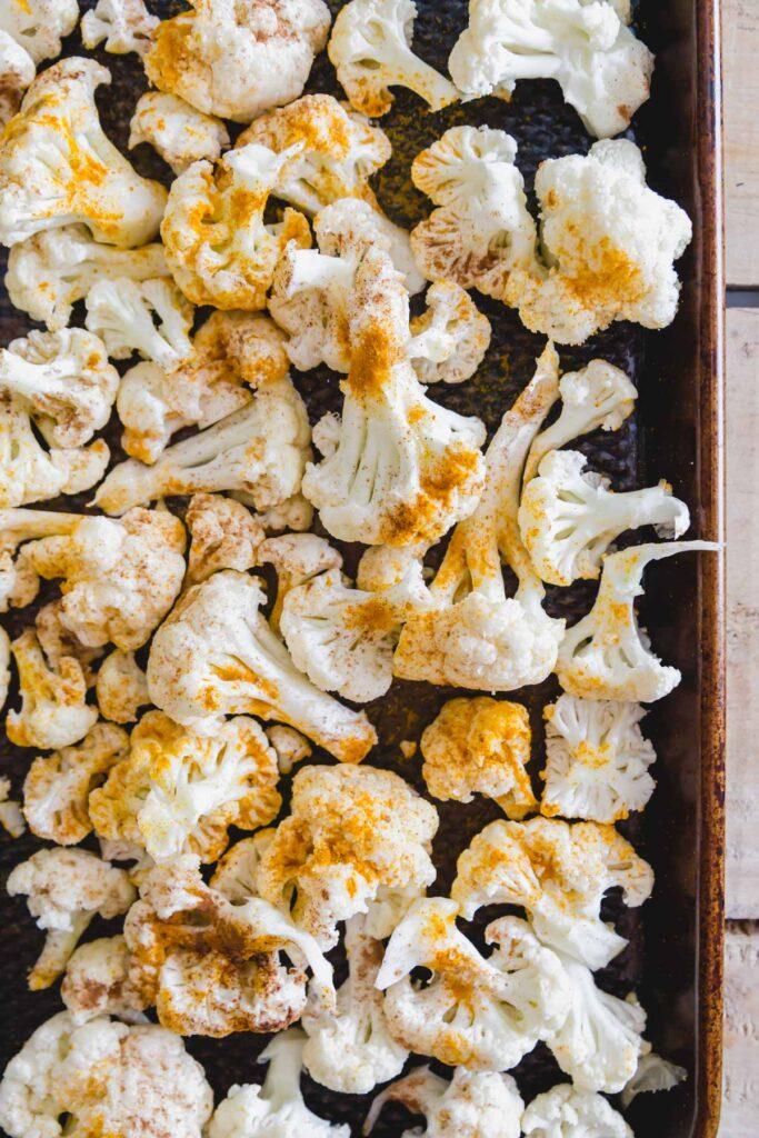 Raw cauliflower florets on a baking sheet seasoned with turmeric and cinnamon.
