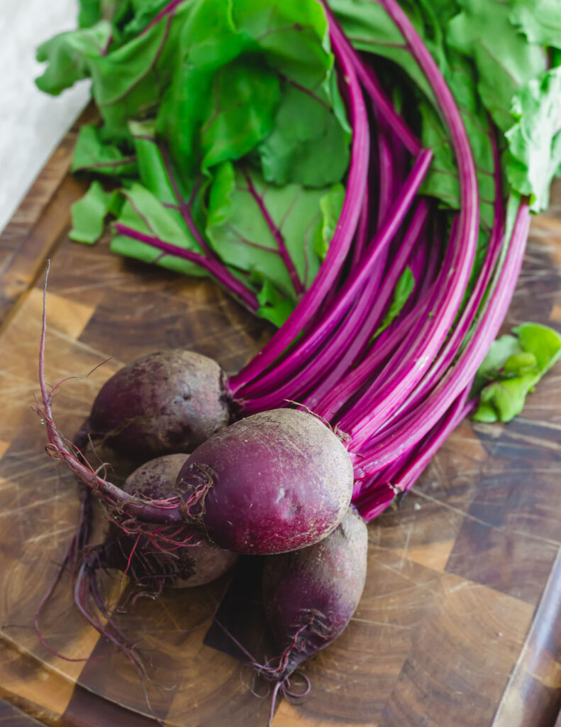 Red beets with greens attached on a cutting board.
