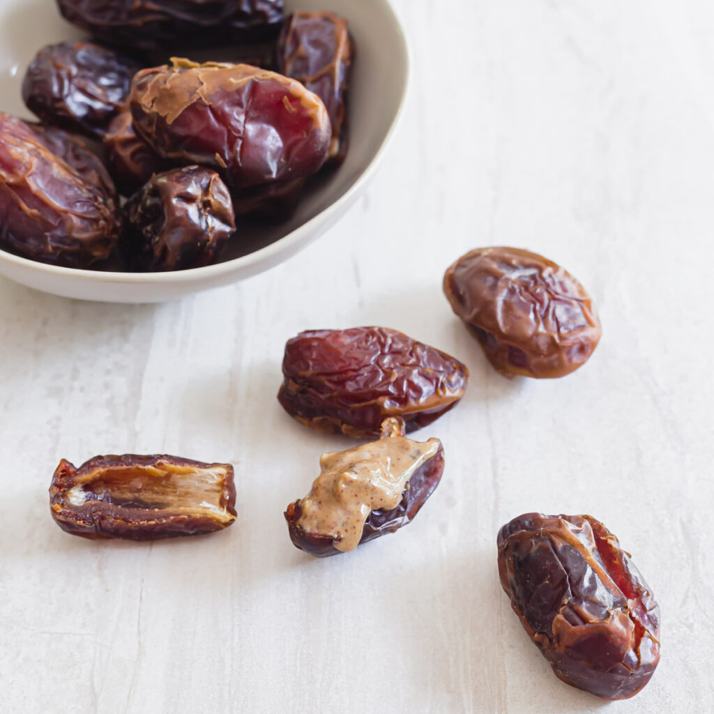 Pitted and halved medjool date stuffed with nut butter.