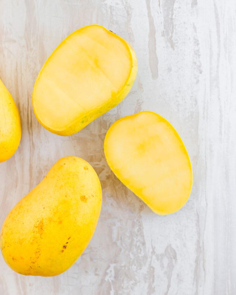 An ataulfo mango sliced in half.