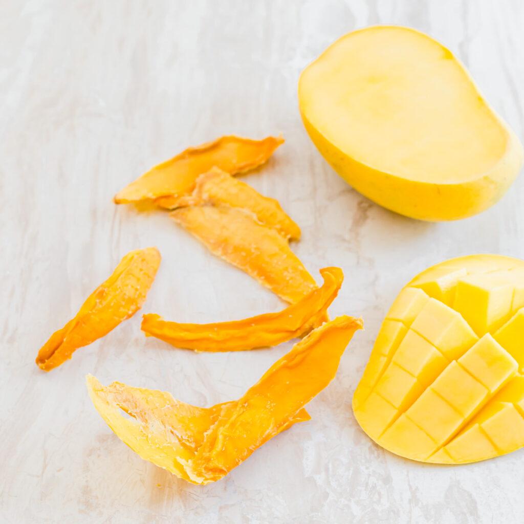 Pieces of dried mango next to half a mango sliced into cubes.