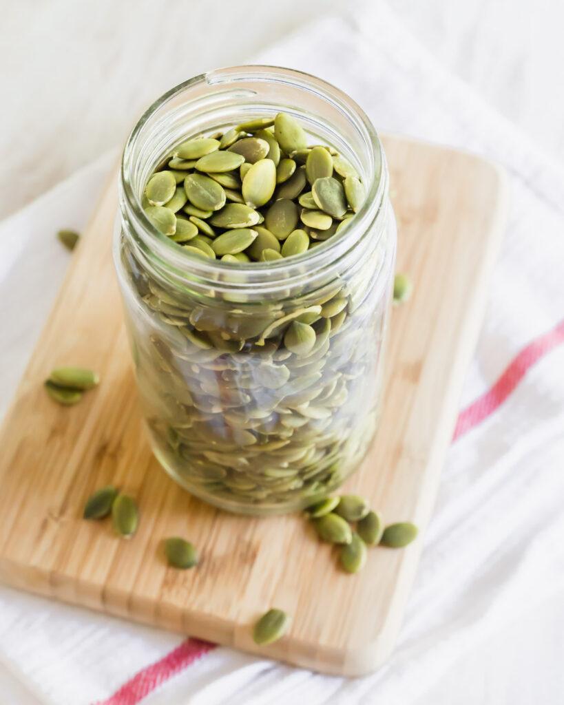 Pumpkin seeds in a glass mason jar.